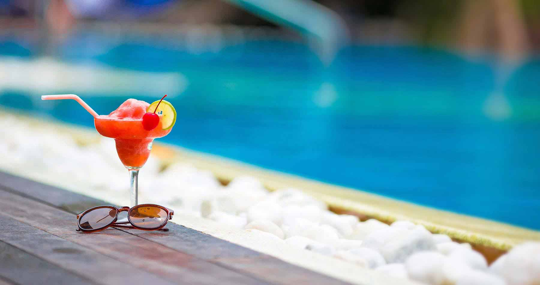 Cocktail and sunglasses on table by pool