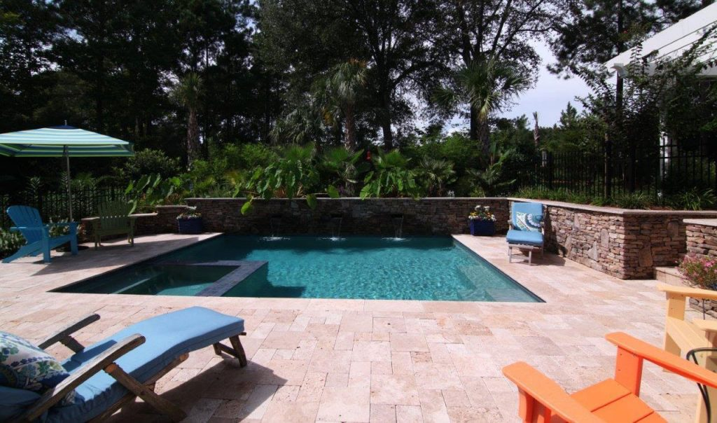 Pool with spa and a stone wall with waterfalls aqua blue for Pool and spa show usa