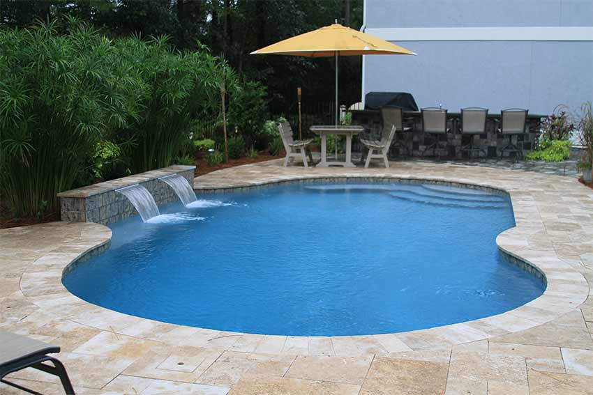 Free form pool with waterfall and umbrella with table
