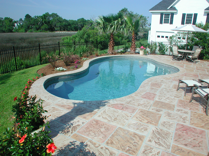 Small free form residential pool with stamped concrete for Residential pools