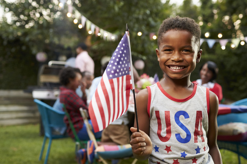 Boy in Patriotic clothes and American flag