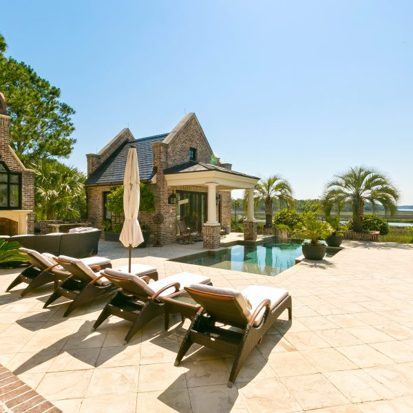 Backyard overview with tanning beds and an infinity pool