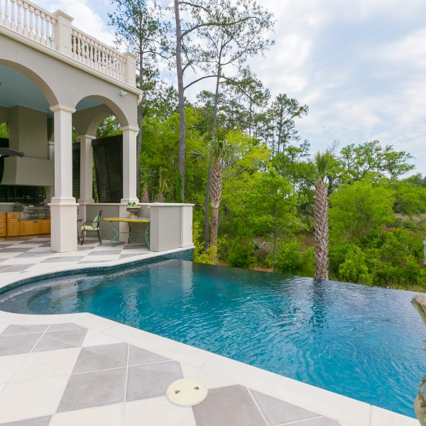 Custom Infinity Pool overlooking a backyard with a statue